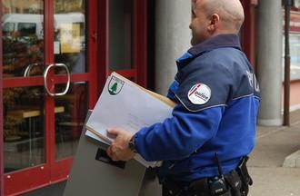 Les assistants de sécurité amènent les enveloppes de vote à La Rebatte à Chézard-St-Martin.