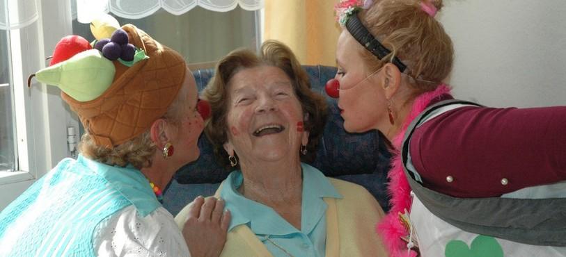 Deux clowns qui embrassent une dame âgée