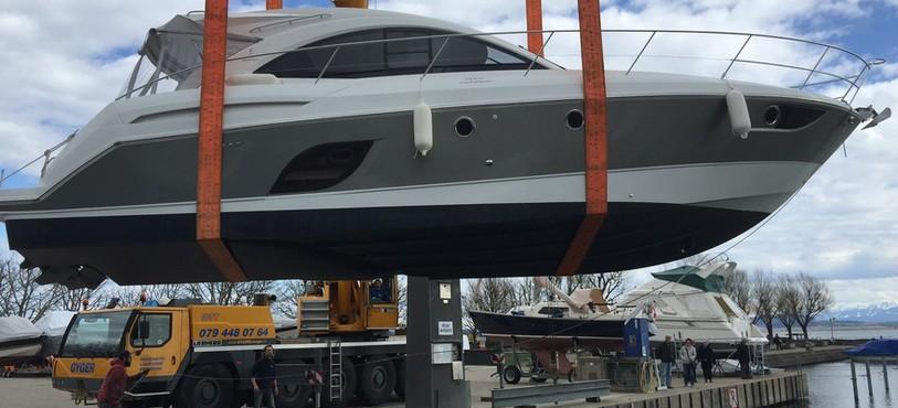 Un yacht est mis à l'eau à l'aide d'un camion-grue dans le port d'Hauterive.
