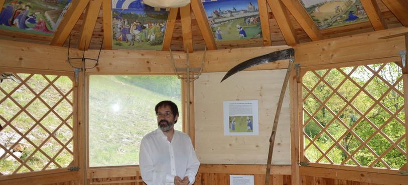 Blaise Mulhauser, directeur du Jardin botanique, sous un calendrier évoquant la vie rurale au 15e siècle.